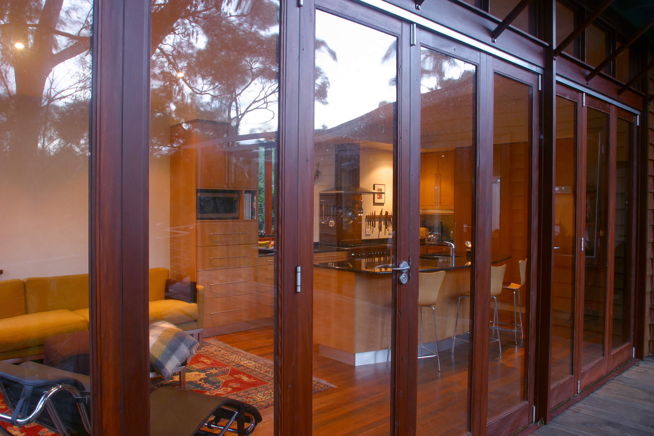 House Butler Extension: Detail of glazed recycled hardwood timber bi-fold doors (mixed eucalyptus) with view to interior recycled hardwood flooring. Photo by Peter Whyte.