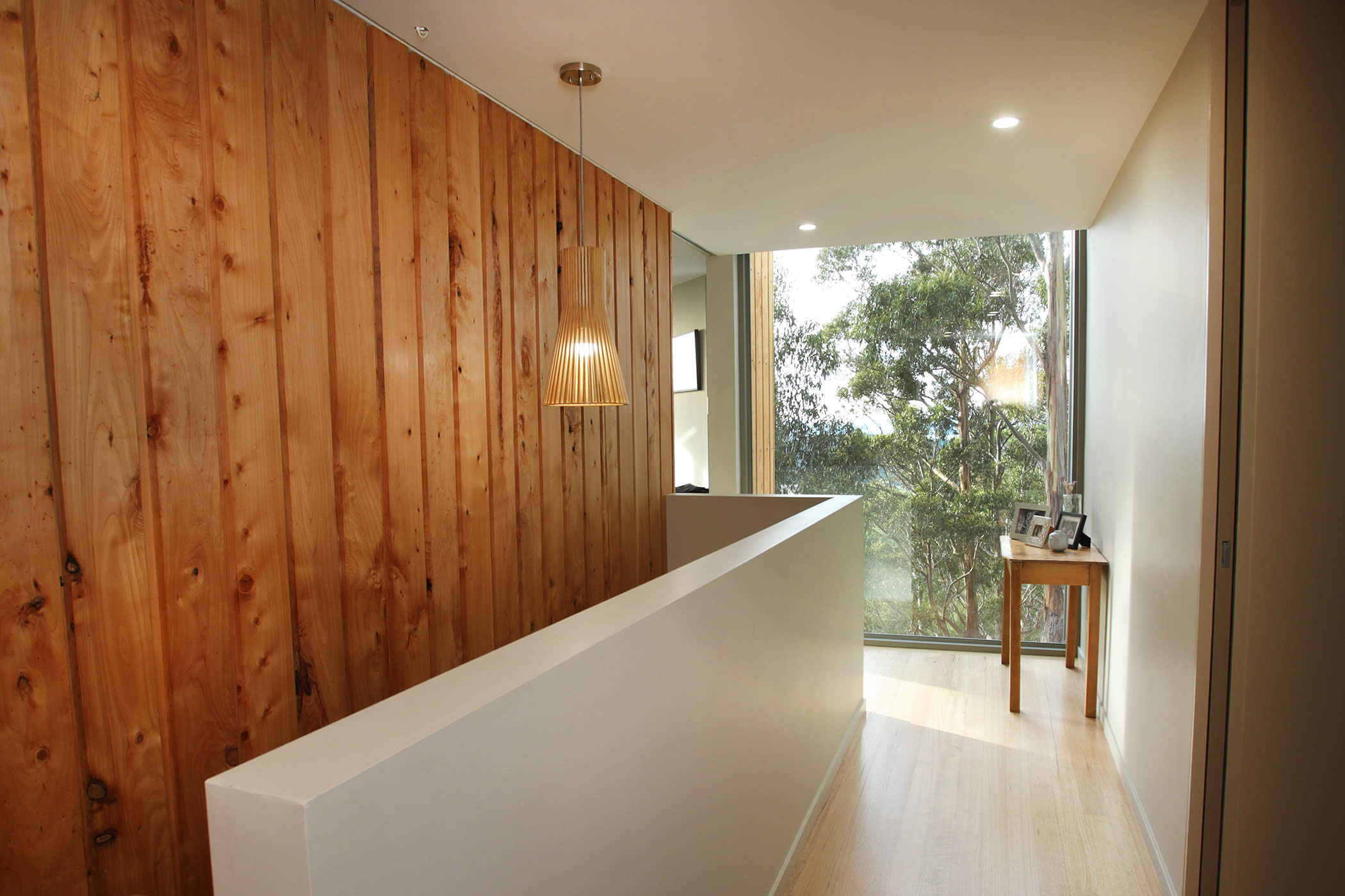 Jamieson Road Residence, Tasmania: We create a memorable effect from the entrance hall by use of natural timber combined with beautiful views through leafy eucalypts to emphasise a natural aesthetic and the country context. Photo by R. Lovell.