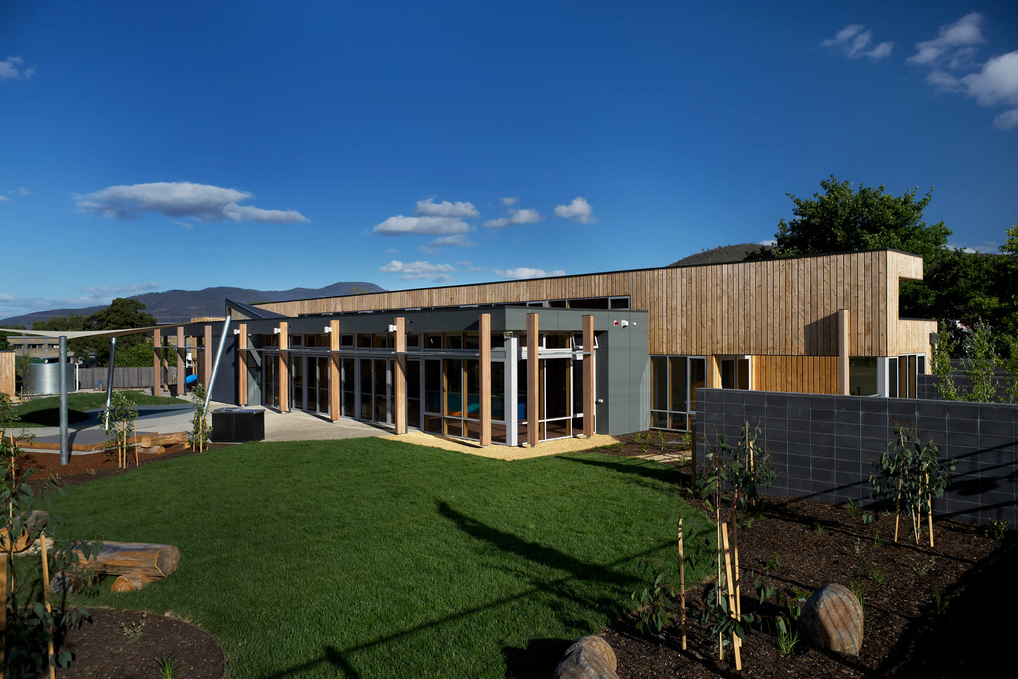 "Ptunarra Child and Family Centre, New Norfolk, Tasmania: Glazed panels and bi-fold doors achieve a ""pavilion in a park"" feel, bring the outside in, and provide passive surveillance and a positive presence to the adjacent playground. Photo by Ray Joyce."