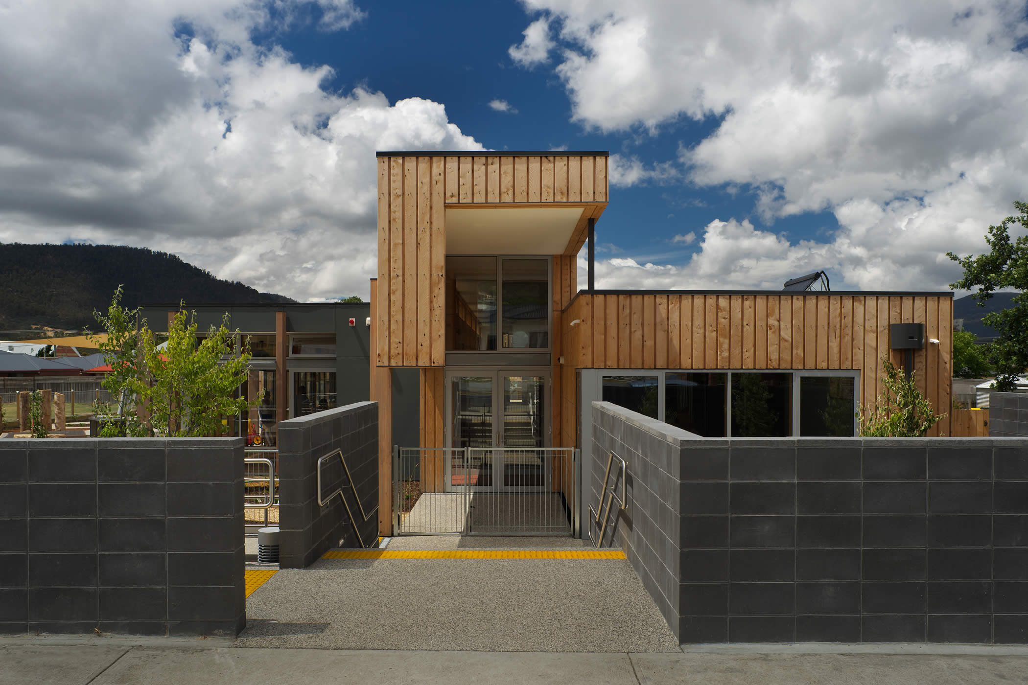 Ptunarra Child and Family Centre, New Norfolk, Tasmania:  The street entrance expresses the interior mezzanine play spine and circulation axis running the building length and introduces the use of external vertical timber cladding. Photo by Ray Joyce.