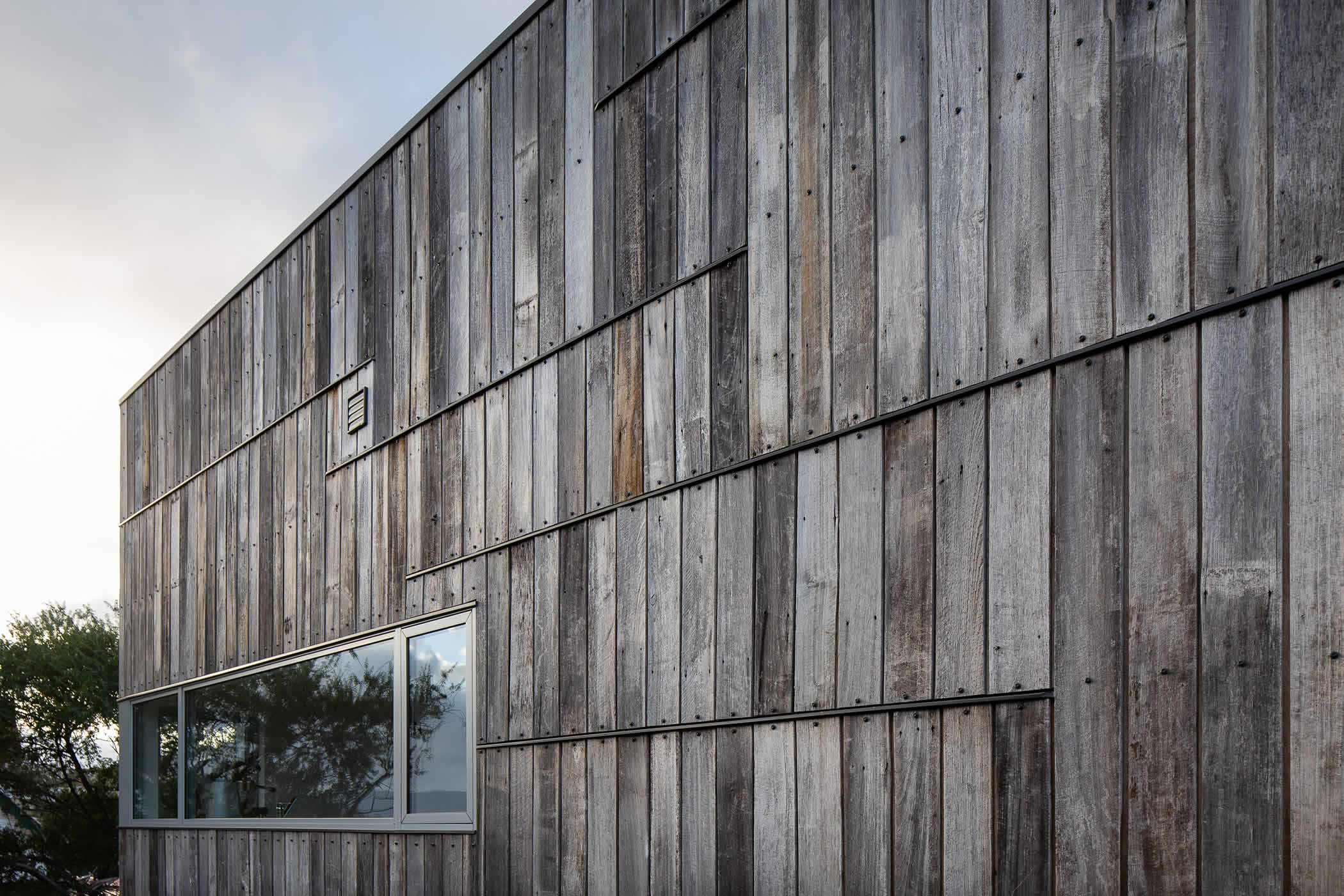 Tiger House, Lindesfarne, Tasmania: Scrap Tas Oak timber fence palings has been salvaged and re-used as external cladding. Weathered timber greys, varied cut down lengths and end capping, create a unique and memorable aesthetic. Photo by Thomas Ryan.