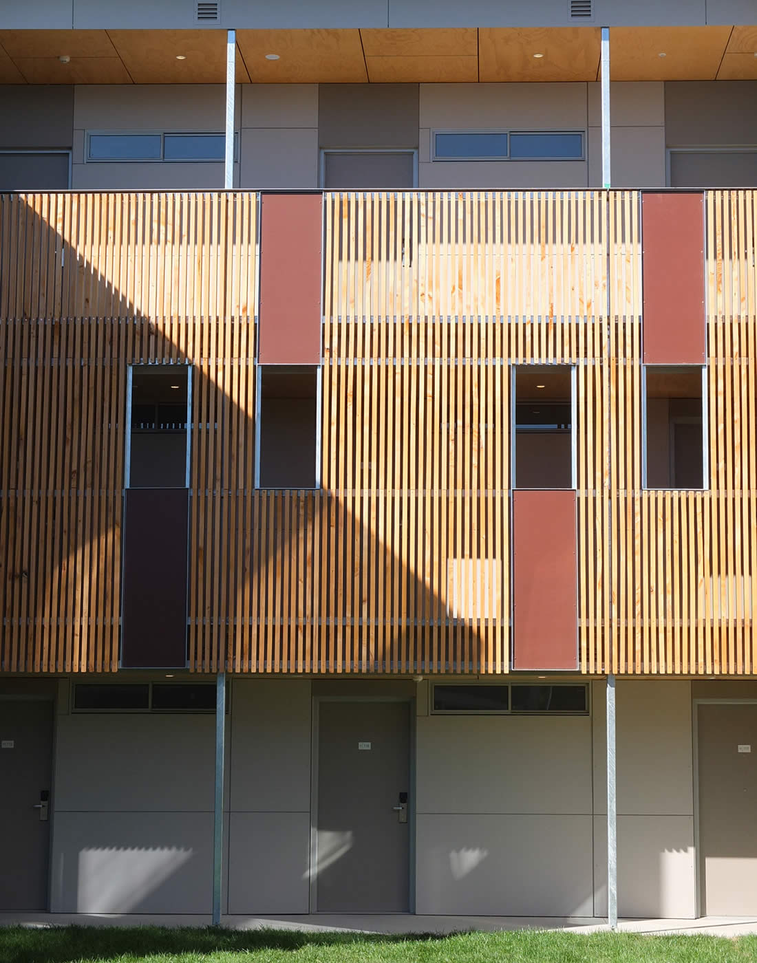 UTAS Newnham Student Residences, Tasmania: Rough sawn unfinished macrocarpa timber screens moderate the weather to open walkways and support crime prevention through environmental design (CPTED) principles. Photo by Morrison & Breytenbach Architects.